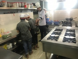 A chef guides two employees