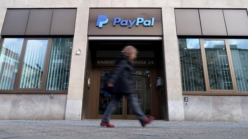 A pedestrian walks past the PayPal logo at an office building in Berlin. PayPal plans to share its financial data with a leading advocacy group in the US to try and stop human traffickers from moving funds on the platform.