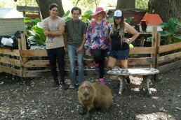 Gabriela Bezeric (2nd R) and her husband Armando Scoppa (2nd L) pose for a photograph with volunteers Facundo Palomino and Yamila Budoff and a rescued capybara at their animal sanctuary