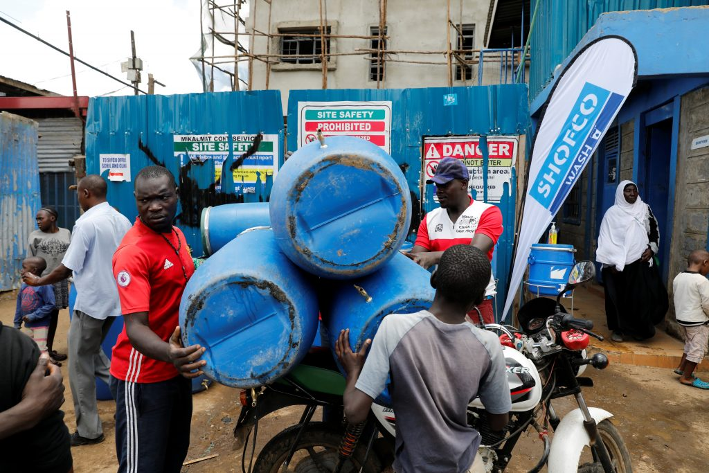 Employees of community organisation Shining Hope for Communities (SHOFCO) load a motorcycle with equipment for hand washing stations against the spread of the coronavirus disease (COVID-19) from their headquarters in the Kibera slum in Nairobi, Kenya, March 18, 2020. REUTERS/Baz Ratner