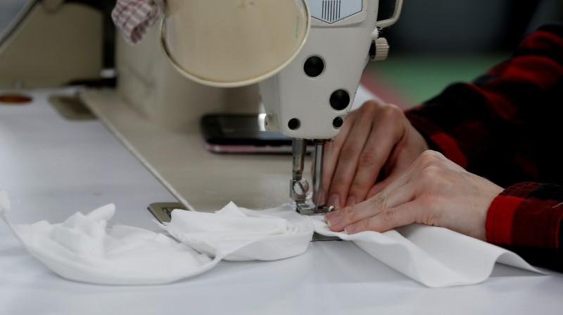 """Elise Thompson sews hospital masks as the spread of coronavirus disease (COVID-19) continues, on day one of turning the """"Detroit Sewn"""" facility into a production facility for hospital masks, in Pontiac, Michigan, U.S. March 23, 2020. REUTERS/Rebecca Cook"""