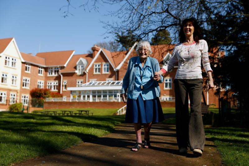 Resident Enid Roche takes a walk in the grounds of Foxholes Care Home, assisted by activities director Susan Davies as the spread of the coronavirus disease (COVID-19) continues, Hitchin, Britain March 25, 2020. Picture taken March 25, 2020. REUTERS/John Sibley