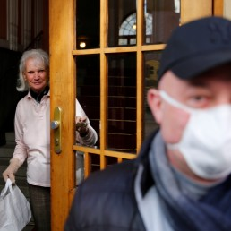 A coachman leaves an elderly woman after delivering a food package during the coronavirus disease (COVID-19) outbreak in Vienna, Austria April 8, 2020. REUTERS/Leonhard Foeger