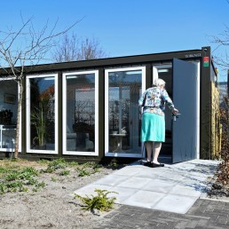 A woman is seen at a care facility for elderly people with dementia, in a glass house that is made especially against loneliness caused by the visit ban due to the coronavirus disease (COVID-19) outbreak in Wassenaar, Netherlands, April 9, 2020. REUTERS/Piroschka van de Wouw