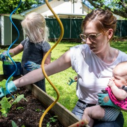 Jaime Calder holds her daughter Lucy while her daughter Billie plants some squash in their vegetable garden in Round Rock, Texas, amid the coronavirus disease (COVID-19) spread in the U.S., April 7, 2020. REUTERS/Sergio Flores