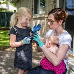 Jaime Calder helps her daughter Billie, 4, put on a gardening glove before planting some squash in her vegetable garden, as she teaches her daughters how to take seedlings out and plant them, amid the coronavirus disease (COVID-19) spread, in Round Rock, Texas, U.S. April 7, 2020. . REUTERS/Sergio Flores