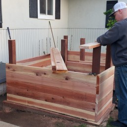 Stephen Curtin builds a raised planter box in his garden in North Ridge, California, U.S., March 18, 2020. Picture taken March 18, 2020. Brittany Carr-Curtin/Handout via REUTERS