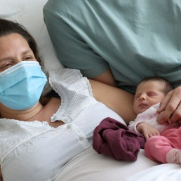 Amandine, who tested positive for the coronavirus disease (COVID-19) just before giving birth, and Francois, wearing protective face masks, are pictured with their newborn daughter Mahaut at the maternity at CHIREC Delta Hospital in Brussels, Belgium April 25, 2020. REUTERS/Yves Herman