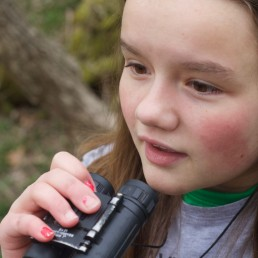 Jordan Miller, 11, birdwatches in her back yard in Manlius, New York, U.S., April 25, 2020 after her Girl Scout troop's group outing to a New York state park was cancelled due to the coronavirus disease (COVID-19) outbreak. Picture taken April 25, 2020. Ashton Miller/Handout via REUTERS