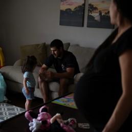Pregnant nurse Samantha Salinas watches as her husband, Tim, entertains their daughter, Macie, amid a coronavirus disease (COVID-19) outbreak in San Antonio, Texas, U.S., May 7, 2020. REUTERS/Callaghan O'Hare