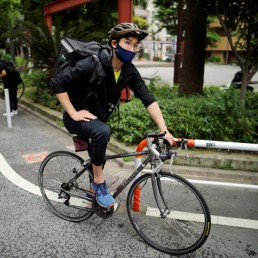 Japan's Olympic fencing medallist Ryo Miyake cycles as he works his part-time job as Uber Eats delivery person under a nationwide state of emergency as the spread of the coronavirus disease (COVID-19) continues in Tokyo, Japan May 12, 2020. REUTERS/Issei Kato
