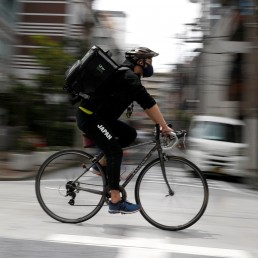 Japan's Olympic fencing medallist Ryo Miyake cycles as he works his part-time job as Uber Eats delivery person under a nationwide state of emergency as the spread of the coronavirus disease (COVID-19) continues in Tokyo, Japan May 12, 2020. Picture taken with a slow shutter speed. Picture taken May 12, 2020. REUTERS/Issei Kato