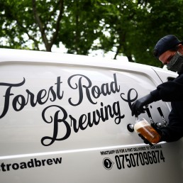 Director of Forest Road Brewing Co Peter Brown pours a customer a pint of beer from the Forest Road Brewing Co pub on wheels vehicle during his delivery round in Hackney, as the coronavirus disease (COVID-19) spread continues in London, Britain, May 12, 2020. REUTERS/Hannah McKay