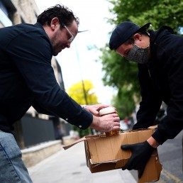 Director of Forest Road Brewing Co Peter Brown carries freshly poured beer to customer Nick Bateson during the delivery round in Hackney, as the coronavirus disease (COVID-19) spread continues in London, Britain, May 12, 2020. REUTERS/Hannah McKay