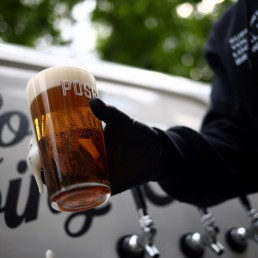 Director of Forest Road Brewing Co Peter Brown carries a freshly poured pint of beer from the Forest Road Brewing Co pub on wheels vehicle during his delivery round in Hackney, as the coronavirus disease (COVID-19) spread continues in London, Britain, May 12, 2020. REUTERS/Hannah McKay