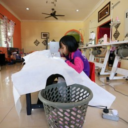 Nur Afia Qistina Zamzuri, a 9-year-old girl sews personal protective equipment (PPE) for free to medical workers working in local hospitals at her home, amid the coronavirus disease (COVID-19) outbreak, in Kuala Pilah, Malaysia May 5, 2020. REUTERS/Lim Huey Teng