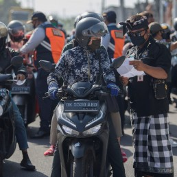 A staff member checks a rider's documents during large-scale social restrictions to prevent the spread of coronavirus disease (COVID-19) in Denpasar, Bali Province, Indonesia May 15, 2020, in this photo taken by Antara Foto. Antara Foto/Nyoman Budhiana/ via REUTERS