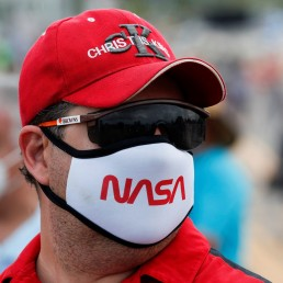 A man wearing a protective face mask attends to view the launch of a SpaceX Falcon 9 rocket and Crew Dragon spacecraft carrying NASA's astronauts Douglas Hurley and Robert Behnken during NASA's SpaceX Demo-2 mission to the International Space Station from NASA's Kennedy Space Center, in Cape Canaveral, Florida, U.S. May 30, 2020. REUTERS/Scott Audette