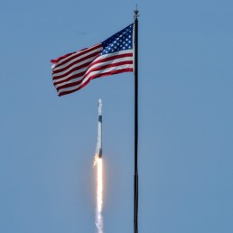 An American flag is seen as SpaceX Falcon 9 rocket and Crew Dragon spacecraft carrying NASA astronauts Douglas Hurley and Robert Behnken lifts off during NASA's SpaceX Demo-2 mission to the International Space Station from NASA's Kennedy Space Center in Cape Canaveral, Florida, U.S. May 30, 2020. REUTERS/Thom Baur