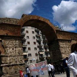 Workers in tourism-related businesses hold a protest as a woman wearing protective face mask walks past the Arch of Galerius following the coronavirus disease (COVID-19) outbreak, in Thessaloniki, Greece, May 28, 2020. REUTERS/Murad Sezer