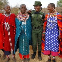 Sharon Karaine, member of Team Lioness, an all-female Kenyan ranger unit, is welcomed by Maasai women in traditional costumes as she arrives home from the Risa camp, where she stayed due to the coronavirus disease (COVID-19) outbreak, within the Olgulului conservancy in Amboseli, Kenya August 8, 2020. Picture taken August 8, 2020. REUTERS/Njeri Mwangi