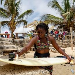 Khadjou Sambe, 25, Senegal's first female professional surfer, waxes her surfboard in Dakar, Senegal, August 13 2020 REUTERS/Zohra Bensemra