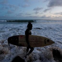 Khadjou Sambe, 25, Senegal's first female professional surfer, carries her surfboard as she walks along the sea at the Secret Beach in Dakar, Senegal, August 14, 2020. REUTERS/Zohra Bensemra