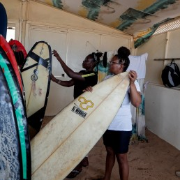 Khadjou Sambe, 25, Senegal's first female professional surfer, checks a surf board as she talks to her coach Rhonda Harper, the founder of Black Girls Surf (BGS), a training school for girls and women who want to compete in professional surfing, in Yoff district, Dakar, Senegal August 1, 2020. REUTERS/Zohra Bensemra