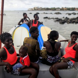 Beginners learning how to surf with Black Girls Surf (BGS), a training school for girls and women who want to compete in professional surfing, sit on a boat as they prepare to attend a training session coached by Khadjou Sambe, Senegal's first female professional surfer, and BSG founder, Rhonda Harper, in Ngor, Dakar, Senegal, August 5, 2020. REUTERS/Zohra Bensemra