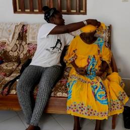 Khadjou Sambe, 25, Senegal's first female professional surfer, adjusts her grandmother Madicke Mbengue's scarf, as they sit inside Sambe's family home in Ngor, Dakar, Senegal, July 29, 2020. REUTERS/Zohra Bensemra