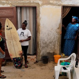 Khadjou Sambe, 25, Senegal's first female professional surfer, holds a surf board as she talks to her coach Rhonda Harper, the founder of Black Girls Surf (BGS), a training school for girls and women who want to compete in professional surfing, as Koune Ba, Sambe's mother, watches on at their courtyard, in Ngor, Dakar, Senegal, August 12, 2020. REUTERS/Zohra Bensemra
