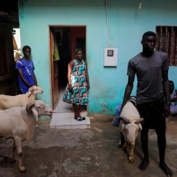 Khadjou Sambe, 25, Senegal's first female professional surfer, watches her relatives prepare to slaughter sheep for a feast of sacrifice during Eid al-Adha, in Ngor, Dakar, Senegal, July 31, 2020. REUTERS/Zohra Bensemra