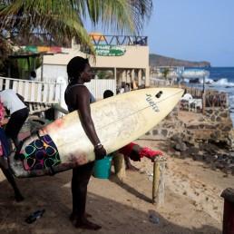 Khadjou Sambe, 25, Senegal's first female professional surfer, holds her surfboard as she watches the sea in Dakar, Senegal, August 12, 2020. REUTERS/Zohra Bensemra