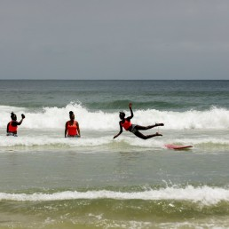 Khadjou Sambe, 25, Senegal's first female professional surfer, and Rhonda Harper, the founder of Black Girls Surf (BGS), a training school for girls and women who want to compete in professional surfing, teach a young surfer during a training session at Yoff district, Dakar, Senegal July 28, 2020 REUTERS/Zohra Bensemra