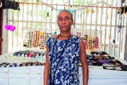 Anne Rose Dorval sells homemade jewelry, watches, scarves and a handful of other fashion items from her small street-side stall in Gonaives, Haiti. FINCA - Global Heroes Magazine 002 - September 2020