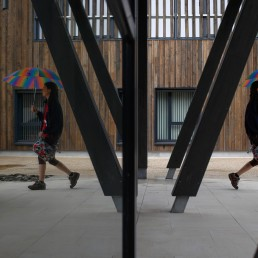 Alzheimer's patient Laetitia, 39, is reflected in a mirror as she walks with an umbrella at the Village Landais Alzheimer site in Dax, France, September 24, 2020. REUTERS/Gonzalo Fuentes