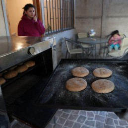 Pedro Campos, who lost his job last year when the restaurant where he worked closed after riots in Santiago broke out over social injustice and entrenched inequality, bakes homemade bread to sell to his neighbours, as his daughter Amelia looks on, at his house at Puente Alto area, on the outskirts of Santiago, Chile October 6, 2020. Picture taken October 6, 2020. REUTERS/Ivan Alvarado