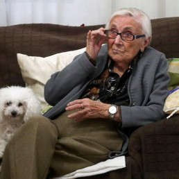 Florentina Martin, a 99 year-old woman who survived coronavirus disease (COVID-19), sits on a sofa with her pet Luna as she watches TV in her home in Pinto, near Madrid, Spain, October 20, 2020. Picture taken October 20, 2020. REUTERS/Sergio Perez