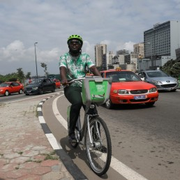 The Ivorian environmental activist Andy Costa also known as the cycling ambassador in Africa, pedals his bike among cars in a street of the central business district of Plateau in Abidjan, Ivory Coast July 24, 2020. REUTERS/Luc Gnago