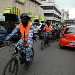 The Ivorian environmental activist Andy Costa also known as the cycling ambassador in Africa, is pictured with municipal police officers of the central business district of Plateau, whose mayor Jacques Gabriel Ehouo supports the concept of using bicycles, in Abidjan, Ivory Coast September 4, 2020. REUTERS/Luc Gnago