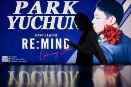 A woman walks past a billboard promoting a K-pop singer Park Yu Chun at the subway in Bangkok, Thailand November 2, 2020. REUTERS/Chalinee Thirasupa
