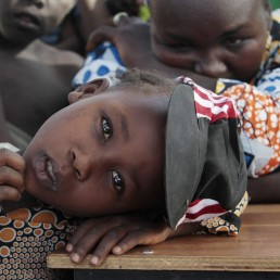 A girl displaced as a result of Boko Haram attack in the northeast region of Nigeria, rests her head on a desk at Maikohi secondary school camp for internally displaced persons (IDP) in Yola, Adamawa State January 13, 2015. Boko Haram says it is building an Islamic state that will revive the glory days of northern Nigeria's medieval Muslim empires, but for those in its territory life is a litany of killings, kidnappings, hunger and economic collapse. Picture taken January 13, 2015. To match Insight NIGERIA-BOKOHARAM/REUTERS/Afolabi Sotunde (NIGERIA - Tags: CIVIL UNREST SOCIETY EDUCATION)