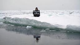 Environmental activist and campaigner Mya-Rose Craig, 18, holds a cardboard sign reading