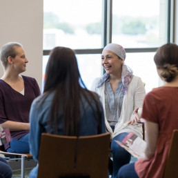 004CA Mature woman wearing a headscarf gestures while discussing chemotherapy treatment with women in a breast cancer support group.