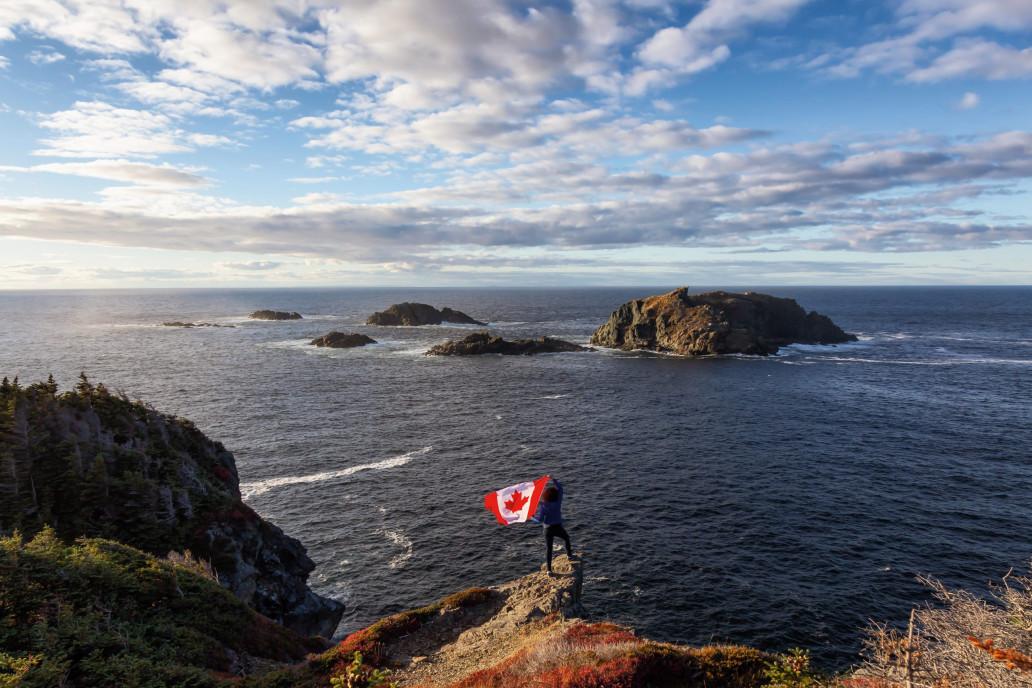 002GHN Adventurous woman holding a Canadian Flag on a Rocky Atlantic Ocean Coast during a sunny day. Taken in Sleepy Cove, Crow Head, Twillingate, Newfoundland, Canada.